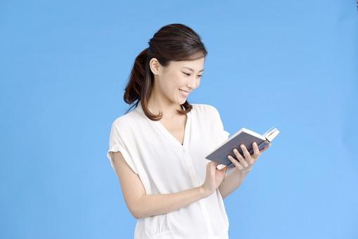 女性 ポーズ 人物 30代 日本人 黒髪 爽やか カジュアル 屋内 横向き 上半身 ブルーバック 青背景 半そで 白  本 見る 読む 持つ 両手 満足 楽しい ブルー 青 ブック 見つめる 読書 mdjf013