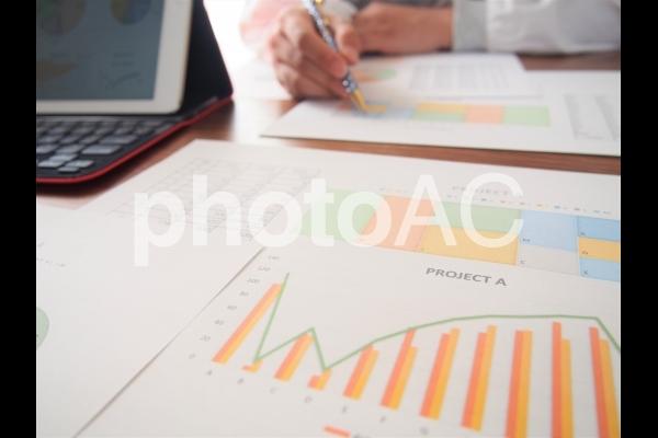 分析資料と向かい合う人の手の写真