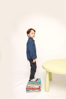 人物 こども 子ども 子供 男の子   少年 幼児 外国人 外人 かわいい   無邪気 あどけない 屋内 スタジオ撮影 白バック   白背景 ポートレート ポーズ キッズモデル 表情  シャツ  カジュアル 全身 立つ テーブル 本 本の上 積み重ねる 踏み台 mdmk010