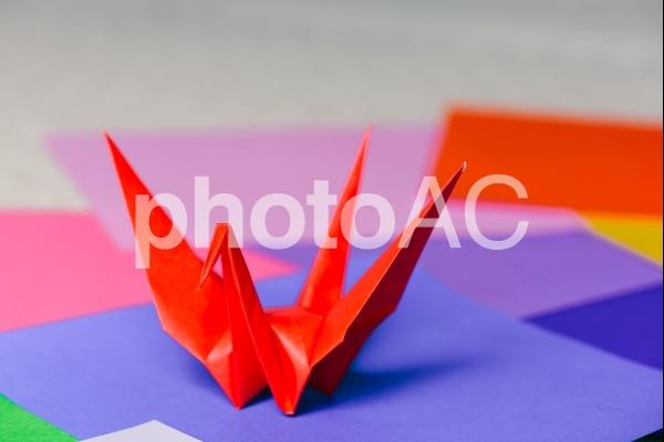 赤い折り鶴とカラフルな折り紙の写真