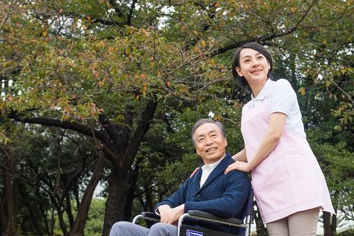 老人 高齢者 お年寄り シニア 男性 男 おとこ  2人 二人  介護士 看護師 エプロン  介護 不自由 椅子 ヘルパー 屋外 緑 木々 木 ジャケット ズボン 青  車いす 車椅子  女性 おんな 女   座る  握る 手 肩 添える 散歩 外出 mdjf017 mdjms004
