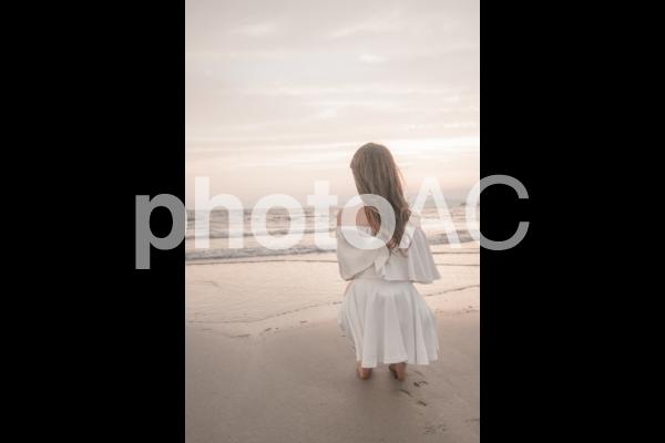夕暮れのビーチと白いドレスの女性の写真
