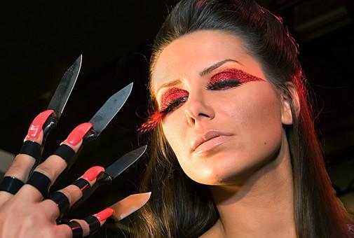 セルビア人 人物 女性 外国人 外人女性 女の人 若い女性 顔 室内 黒髪 黒髪女性 化粧 厚化粧 メイク 黒バック 黒背景 刃物 ナイフ 指 凶器 危険 赤いメイク アイシャドウ ラメメイク 危険