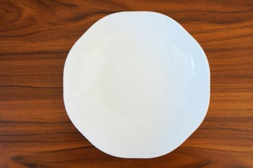 木目テーブルの上の白い皿の写真