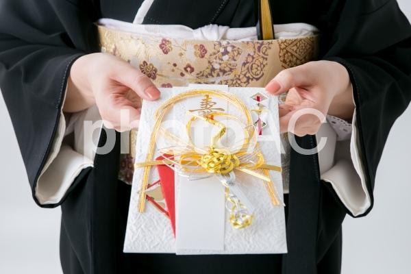 お祝儀を差し出す黒留袖の女性の写真