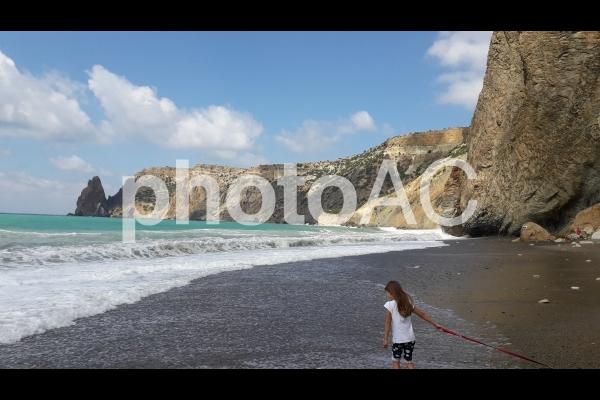 高波の海と海辺を歩く少女の写真