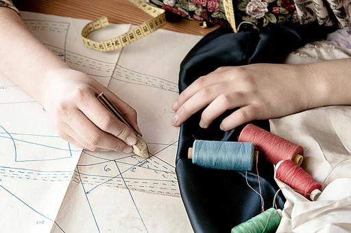 屋内 室内 裁縫 洋裁 ソーイング 縫製 服 洋服 服作り 手芸 クラフト ハンドクラフト 家事 作業 仕事 デザイナー 型紙 パターン チャコ 生地 布 印 印をつける 書く 描く 線を引く 手 手元 メジャー 糸 糸巻き ミシン糸