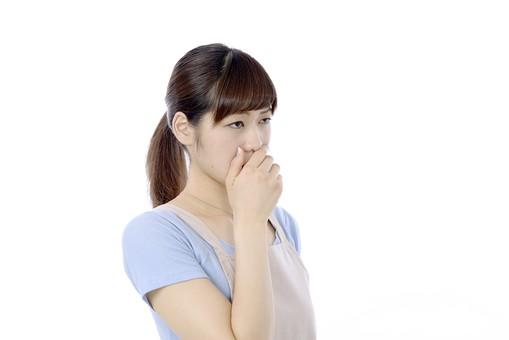 人物 屋内 白バック 白背景 日本人 1人 女性 20代 30代 エプロン  奥さん 奥様 婦人 家庭人 夫人 主婦 若い ポーズ 手 口 覆う 口を手で覆う におい 臭い 臭う 異臭 口臭 変な表情 mdjf018
