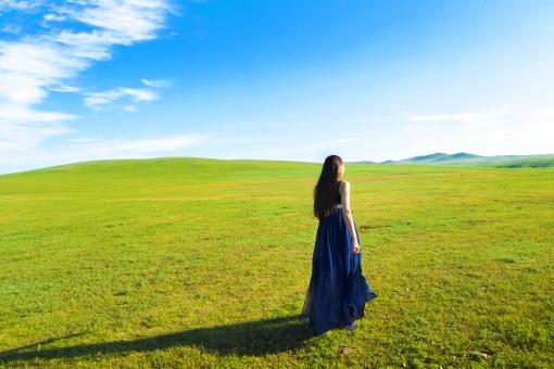モンゴルの大地を眺める青いドレスの女性の写真