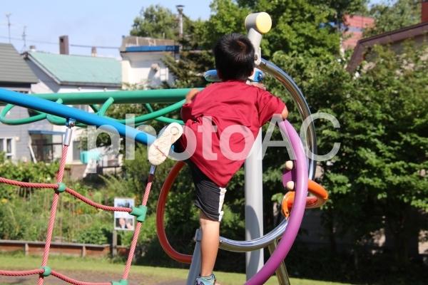公園の遊具で遊ぶ男の子の写真