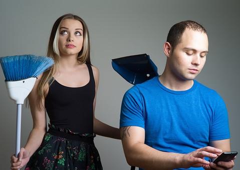 屋内 人物 外国人 女性 男性 大人 2人 若い 若者 20代 カップル 夫婦 ペア 黒 青 見る 掃除道具 ほうき 持つ 家事 塵取り 分担 無関心 うつむく 下を向く スマートフォン スマホ すれ違い 不機嫌 寂しい 恋人 mdff023 mdfm013