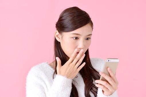 人物 女性 日本人 若者 若い  20代 美人 かわいい ロングヘア カジュアル  ラフ 私服 セーター ニット 屋内  スタジオ撮影 背景 ピンク ピンクバック ポーズ  おすすめ 上半身 スマホ スマートフォン 携帯 電話 見る 驚く びっくり ビックリ mdjf007