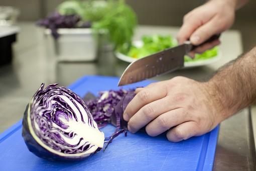 厨房 台所 キッチン 料理 調理  コック シェフ 料理人 包丁 ナイフ 切る カット まな板 レストラン 仕込み 下準備 野菜 青 バット ボディパーツ 腕 持つ 手 紫キャベツ レッドキャベツ 赤きゃべつ  千切り 細かい 細かく 手元 男性 外国人