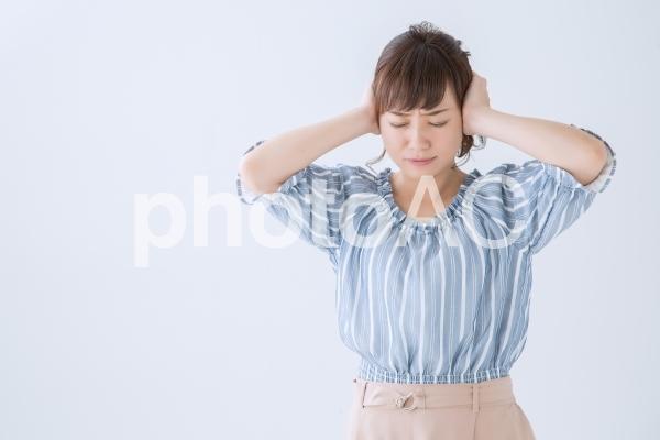 耳をおさえる女性の写真