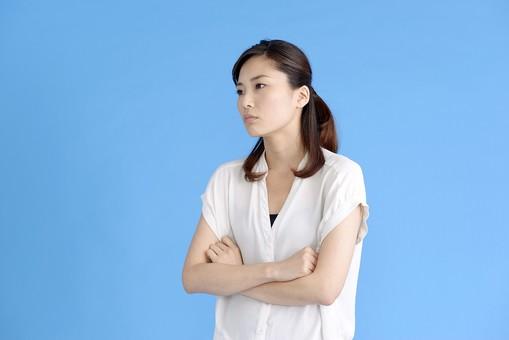 女性 ポーズ 人物 30代 日本人 黒髪 爽やか カジュアル 屋内 正面 ブルーバック 青背景 半そで 白  怒り 怒る  腹立たしい 両手 上半身 腕組 ふん 憤慨 なにそれ 睨む 睨みを利かせる 脅し 圧力 我慢 忍耐 腕組み mdjf013