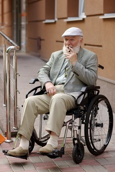 病院 医院 診療所 屋外 外 外国人 白人 男性 老人 高齢 高齢者 おじいさん おじいちゃん 髭 ヒゲ ひげ 白髪 車椅子 車いす 座る 乗る 乗せる 上着 ジャケット ハンチング帽 全身 カメラ目線 たばこ タバコ 煙草 葉巻 葉巻き 吸う mdjms016