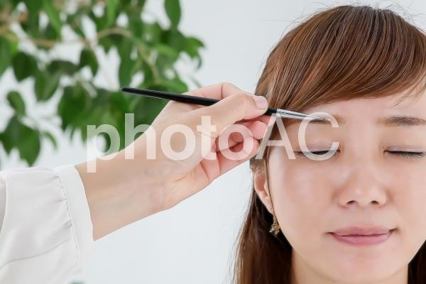 まゆげを書かれる女性の写真