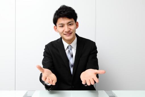人物 生物 人間 男性 若い 青年 アジア アジア人 日本 日本人 オフィス  仕事 ビジネス ビジネスマン 職業 スーツ フォーマル 会社 働く 座る デスク 正面 微笑む 笑顔 休憩 手を広げる mdjm002
