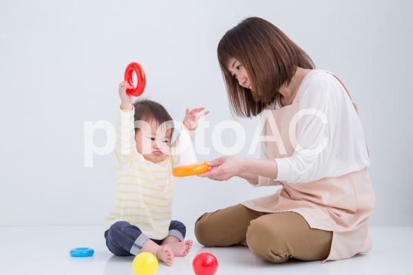 赤ちゃんと遊ぶエプロン姿の女性の写真