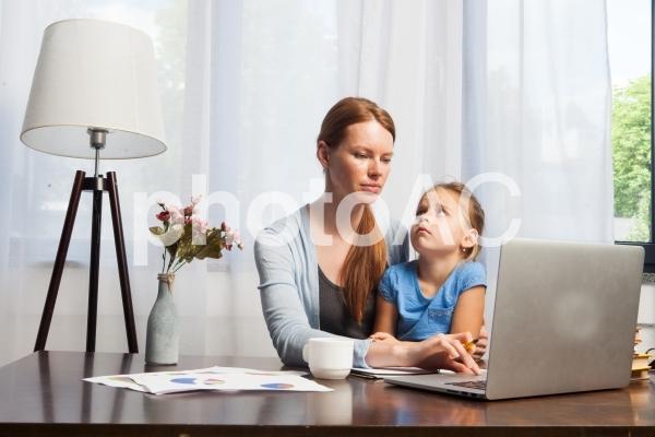 自宅で娘を抱っこしながら仕事するお母さん4の写真