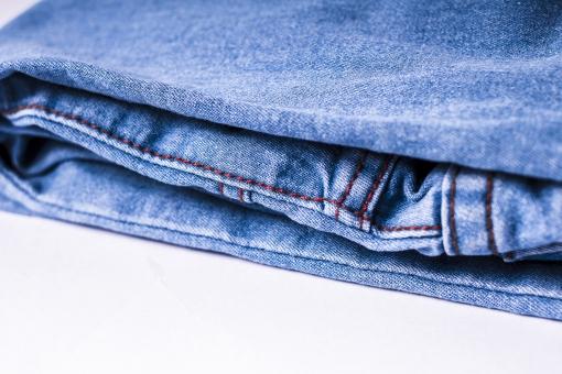 ジーンズ ジーパン Gパン デニム 柄 無地 生地 裾 布 布地 折り畳み 畳む ファッション パンツ 縫目 縫い目 白背景 足 脚 ミシン 服装 服 ズボン 青 ブルー 水色 裁縫