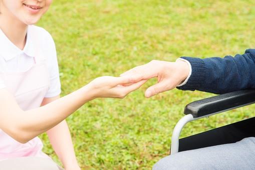 老人 高齢者 お年寄り シニア 男性 男 おとこ  2人 二人  介護士 看護師 エプロン  散歩 外出 介護 不自由 椅子 ヘルパー 屋外 緑 木々 木 ジャケット ズボン 青  車いす 車椅子    座る  握る 手 白衣 エプロン ピンク  アップ