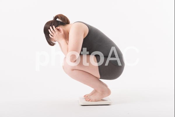 体重計にのり困っている女性2の写真