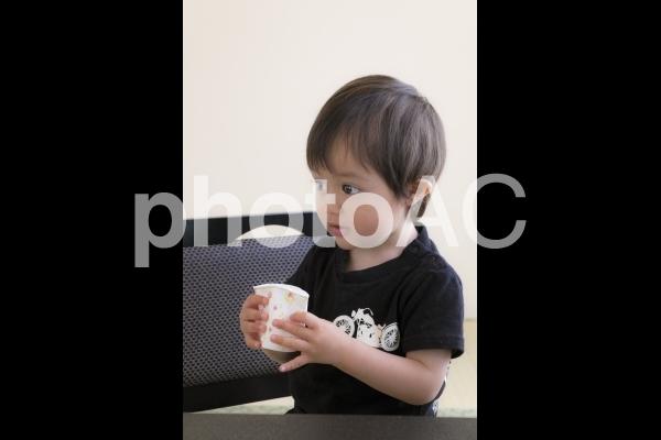 紙コップをつぶす2歳児の写真
