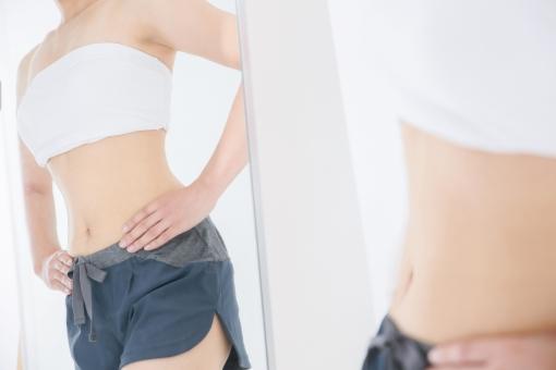 鏡越しに体を見る女性の写真