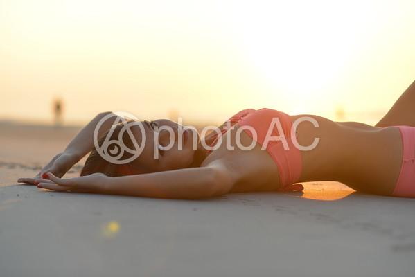 ビーチに寝転がる水着を着た外国人女性2の写真
