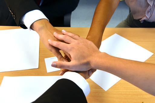 会社 オフィス ビジネス 仕事 職場 屋内 室内 働く  人物  相談 会議  結束 重ねた手 ハンドパーツ 手 奮闘 努力 円陣 チーム デスク 資料 テーブル チームワーク 気合い 団結 成功 ファイト