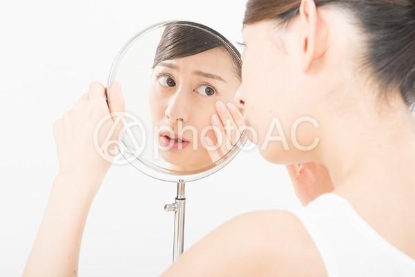 鏡で肌をチェックする女性(鏡越し)7の写真
