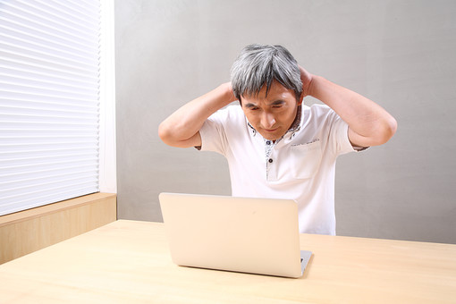 シニア 老人 おじいちゃん ライフスタイル 趣味 PC 生涯学習 習う おじいさん 白髪 机 ノートパソコン ポロシャツ 頭 抱える 悩む 頭痛 困る 困った 人物 男性 日本人 60代 パソコン わからない 生活 暮らし シニアライフ WEBサイト mdjm013