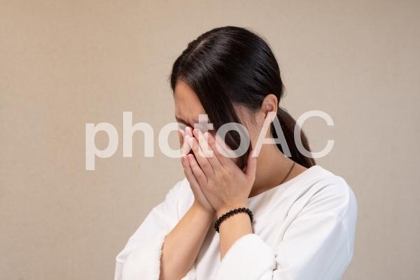 顔を手で覆って泣く女性の写真