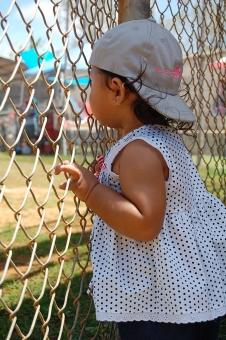 野球 幼児 子供 フェンス 草野球 応援 覗き見 帽子 夏 風 見る 鑑賞 水玉 女子 少女 赤ちゃん 試合 ゲーム スポーツ観戦 baby watching kid child summer fence baseball cap wind polkadots girl
