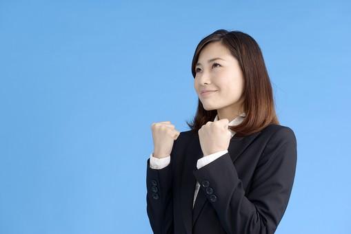 人物 女性 日本人 20代 若者  ビジネス スーツ 黒 紺色 セミロング  OL 社会人 会社員 ビジネスマン 就活  就職活動 真面目 ポーズ 屋内 スタジオ撮影  ブルーバック 上半身 ガッツポーズ 応援 励ます 張り切る 頑張る やる気 両手 横向き 笑顔 コピースペース mdjf013