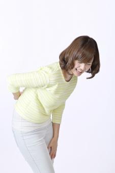 人物 女性 女の子 若い 若者   20代 日本人 屋内 スタジオ撮影 白バック   白背景 ジェスチャー 仕草 かわいい 可愛い ポーズ 表情 痛み 痛い 苦しい 辛い 腰 腰痛 ぎっくり腰 しかめる 病気 手を当てる 健康 mdjf003