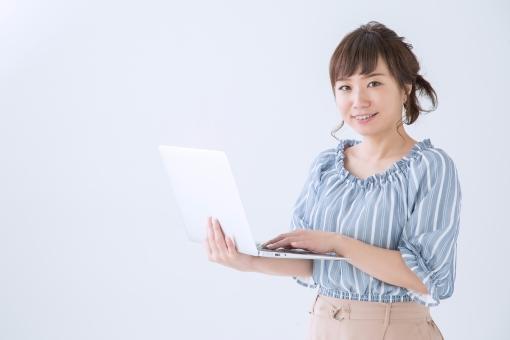 ノートパソコンと女性(笑顔)の写真