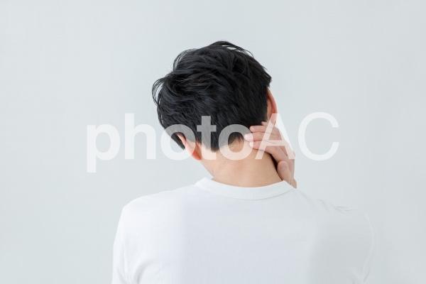 首をおさえる男性の写真