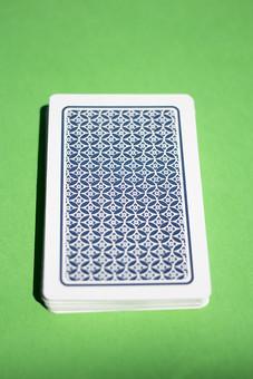 トランプ カード ゲーム 札 屋内 グリーンバック 緑背景 娯楽 机 テーブル 裏側 裏 青 模様 束   緑  絵札   手品 マジック 遊び 絵札  重ねる 配る 切る カードゲーム
