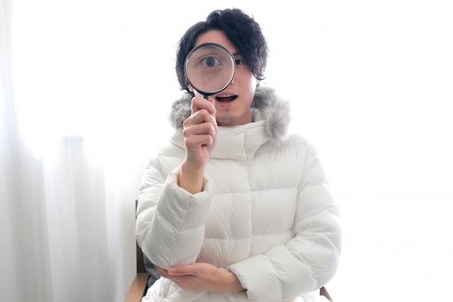 虫眼鏡を覗く男性の写真
