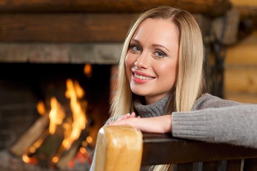 外国人 20代 若い 女性 女 金髪 ロングヘアー 笑う 笑顔 スマイル 微笑み 上半身 室内 冬 ウィンター  クリスマス 寄りかかる 凭れる 凭れかかる リラックス 寛ぐ 接写 クローズアップ 背もたれ 腕 片腕 乗せる 首をかしげる 背景 暖炉 炎 火 mdff095