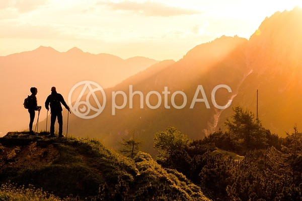 朝日の中トレッキングをする男女4の写真