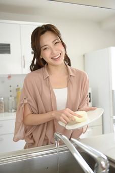 日本人 女性 女 30代 アラサー ライフスタイル 部屋 室内 ポーズ ピンクベージュ ピンク チュニック  カジュアル プライベート 部屋着 私服  キッチン  主婦  ハーフアップ シンク 皿洗い 洗い物 後片付け 片づけ お片付け 笑顔 スマイル 食器 洗う mdjf013