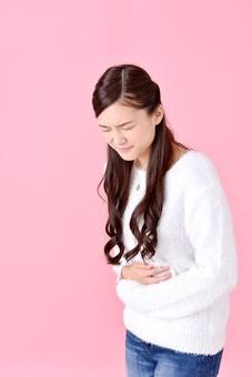 人物 女性 日本人 若者 若い   20代 美人 かわいい ロングヘア カジュアル  ラフ 私服 セーター ニット 屋内  スタジオ撮影 背景 ピンク ピンクバック ポーズ  おすすめ 上半身 お腹 押さえる 腹痛 痛い 体調不良 苦しい 辛い mdjf007