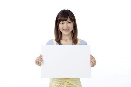 人物 屋内 白バック 白背景 日本人 1人 女性 20代 30代 エプロン  奥さん 奥様 婦人 家庭人 夫人 主婦 若い ポーズ 表情 笑顔 微笑む 手 両手 持つ パネル 白紙 メッセージボード ボード スペース 余白 mdjf018