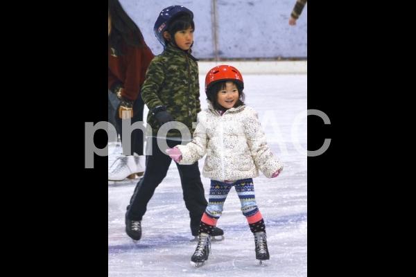 アイススケートを楽しむ兄妹の写真