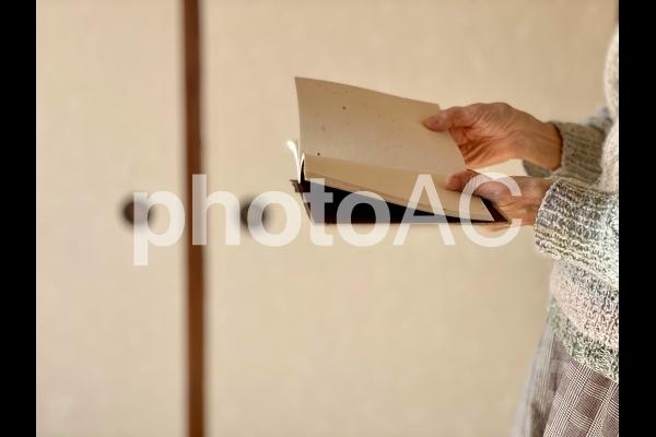 ふすまの前で本を読む高齢者の写真