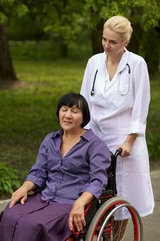 屋外 野外 外 病院 庭 公園 外国人 老人 高齢者 女性 おばあさん おばあちゃん 患者 女医 白人 金髪 白衣 医師 医者 スカート 車椅子 車いす 乗る 座る 押す 散歩 歩く 立ち止まる 止まる mdfs016 mdff142