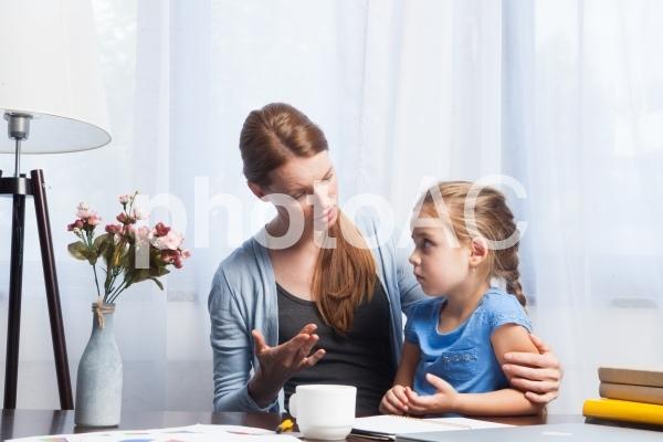 自宅で娘に邪魔されながら仕事するお母さん2の写真